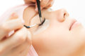 Eyelash Extension Procedure.  Woman Eye with Long Eyelashes. Royalty Free Stock Photo