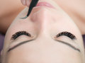 Eyelash Extension Procedure. Woman Eye with Long Eyelashes.