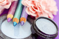 Eyepencils and eyeshadows on purple with petals Royalty Free Stock Photos