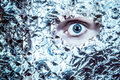 The eyes have it an eye peeks out of a mask of tin foil looks frightening and surreal split colortone Royalty Free Stock Images