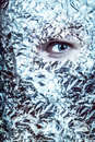 The eyes have it an eye peeks out of a mask of tin foil looks frightening and surreal split colortone Royalty Free Stock Photography