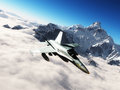 F hornet a multi role fighter flying above the clouds in the background are snowy mountain peaks Royalty Free Stock Photography