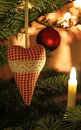 Fabric heart on a christmas tree with lights and bauble in background Royalty Free Stock Photos