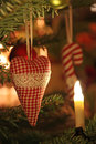 Fabric heart on a christmas tree with lights and candy cane at the background Royalty Free Stock Image