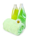 Fabric softener in two bottles with chamomile of yellow and green green towel camomile a light shade on white background Stock Image