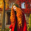 Fabulous redhead woman with long curly hair in a red coat and a green turban on a bright autumn background.
