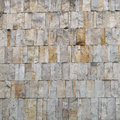 Facade cladding or wall finishing of pale ocher stone building background texture natural rough in material for Royalty Free Stock Image