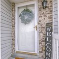 Facade of home with a leafy wreath hanging between the glass and wooden door Royalty Free Stock Photo