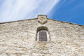 Facade of medieval church with window and cross shape Royalty Free Stock Photo