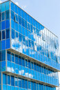 Facade of a modern building. Glass Windows reflected the sky and clouds. Blue gamma Royalty Free Stock Photo