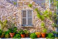 The facade of an old stone house with wooden brown shutter and flowerpots