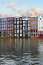 Facades of historic buildings amsterdam over canal waters netherlands Royalty Free Stock Images