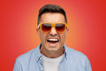 Face of angry man in shirt and sunglasses over red Royalty Free Stock Photo