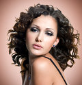 Face of beautiful adult woman with curly hairs over brown background Stock Photos