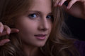 Face of a beautiful blond girl looking seductively straight to the camera dark tones low key Stock Photography