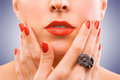 Face and beautiful red manicure on the blue Royalty Free Stock Photo