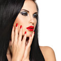 Face of a beautiful woman with red nails and lips closeup brunette isolated on white background Royalty Free Stock Photos