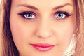 Face of a beautiful young woman with blue eyes closeup Royalty Free Stock Photography