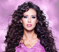 Face of a beautiful young woman with long hairs brown ringlets and fashion makeup Stock Images