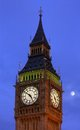 The face of big ben at westminster at dusk with the moon in view and a deep blue sky Stock Photography