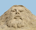 Face carved in a sand pile of against blue sky depiction of christ Stock Images
