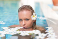 Face of a female model in the pool with white water flowers