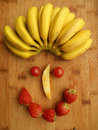 Face of fruits this is a happy it is made strawberry banana pineapple and small tomatoes Stock Image