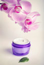 Face/hand cream jar and purple orchid flowers, vertical shot Royalty Free Stock Image