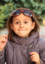Face of little girl with glasses smiling kid big rolling eyes and sun on head Royalty Free Stock Images