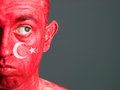 Face man turkish flag and distrustful expression makeup with isolated on dark background Stock Image