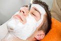 Face mask therapist applying a to a beautiful young man in a spa using a cosmetics brush Royalty Free Stock Images