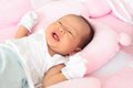 Face New born infant lied on pink bed Royalty Free Stock Photo