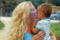 Face-painted mother kissing her little child Stock Photo