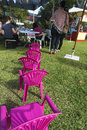 Face painting a row of chairs waiting to be filled with children at a school fair with the sign and parents standing around Royalty Free Stock Images