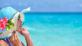 Face woman is happy with the sea in thailand young wearing sun protection hat to see beautiful nature of under summer sky at koh Royalty Free Stock Photos