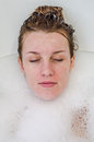 Face of a young beautiful girl in a white bath among soap bubbles from the foam bath gel, naked with wet hair, enjoys the spa trea Royalty Free Stock Photo