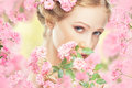 Face of young beautiful woman with pink flowers