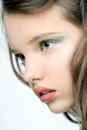 The face of a young girl with bright makeup on eyes. Royalty Free Stock Photo