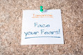 Face your fears reminder for tomorrow on paper pinned on cork board a Royalty Free Stock Photo