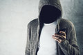 Faceless hooded person using mobile phone, identity theft concep Royalty Free Stock Photo