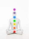 Faceless man chakra graphics dressed in white sitting in yoga lotus position with colored Stock Images