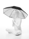 Faceless man umbrella lotus dressed in white sitting on the floor with an over his head Royalty Free Stock Photos