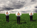 Faceless men standing on the green field man and holding images with different emotions Stock Photography