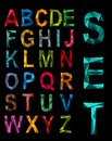 Faceted complete origami alphabet set in the colours of the rainbow in uppercase on a black background Royalty Free Stock Photography