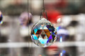 Faceted crystal hanging ball reflecting colorful light off the facets on wire close up with copy space Stock Photo