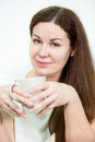 Facial portrait of young woman with tea mug in hands, grey background Royalty Free Stock Photo