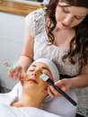 Facial in the salon photo of a young beautiful girl receiving a green mask spa beauty Royalty Free Stock Photography