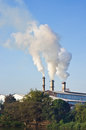 Factory smokestack three of against morning sunlight Stock Photos