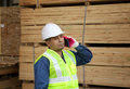 Factory worker mature talking with mobile phone standing beside stacking wood Stock Photos