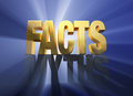 Facts vanquish myths bright gold atop a dark gray on a dark blue background brilliantly backlit with light rays shining through Stock Photos